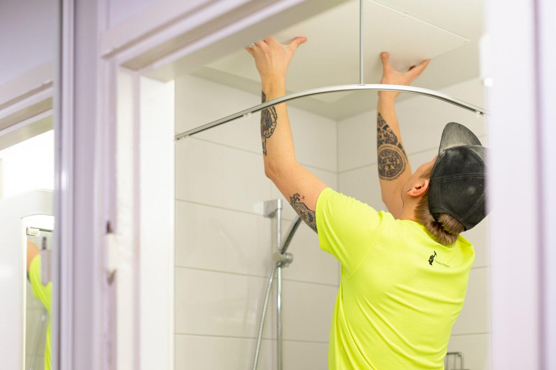 Respect Project työntekijä asettamassa kylpyhuoneen yläpaneeleja